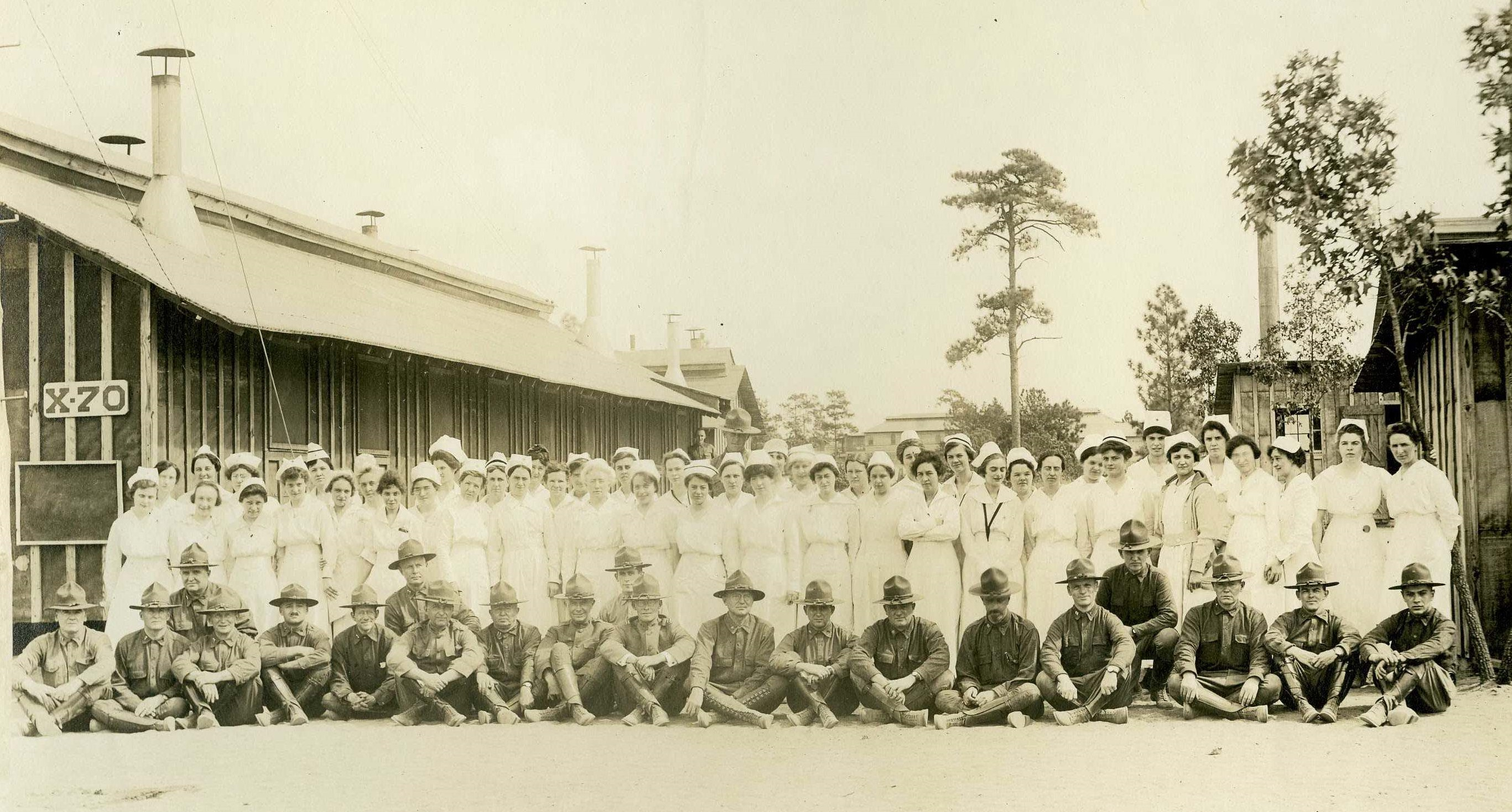 Females nurses standing in back row, male medical officers seated in front row, outside at Camp Jackson Base Hospital.