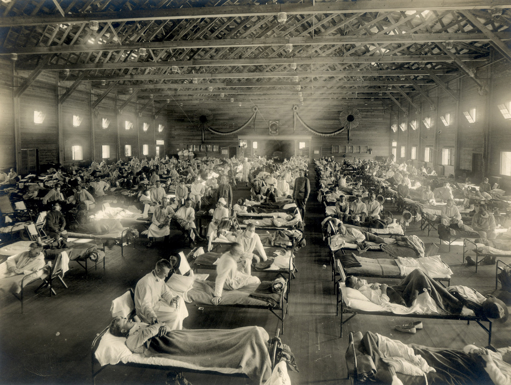 Rows of cots with influenza patients cover the floor of emergency hospital.
